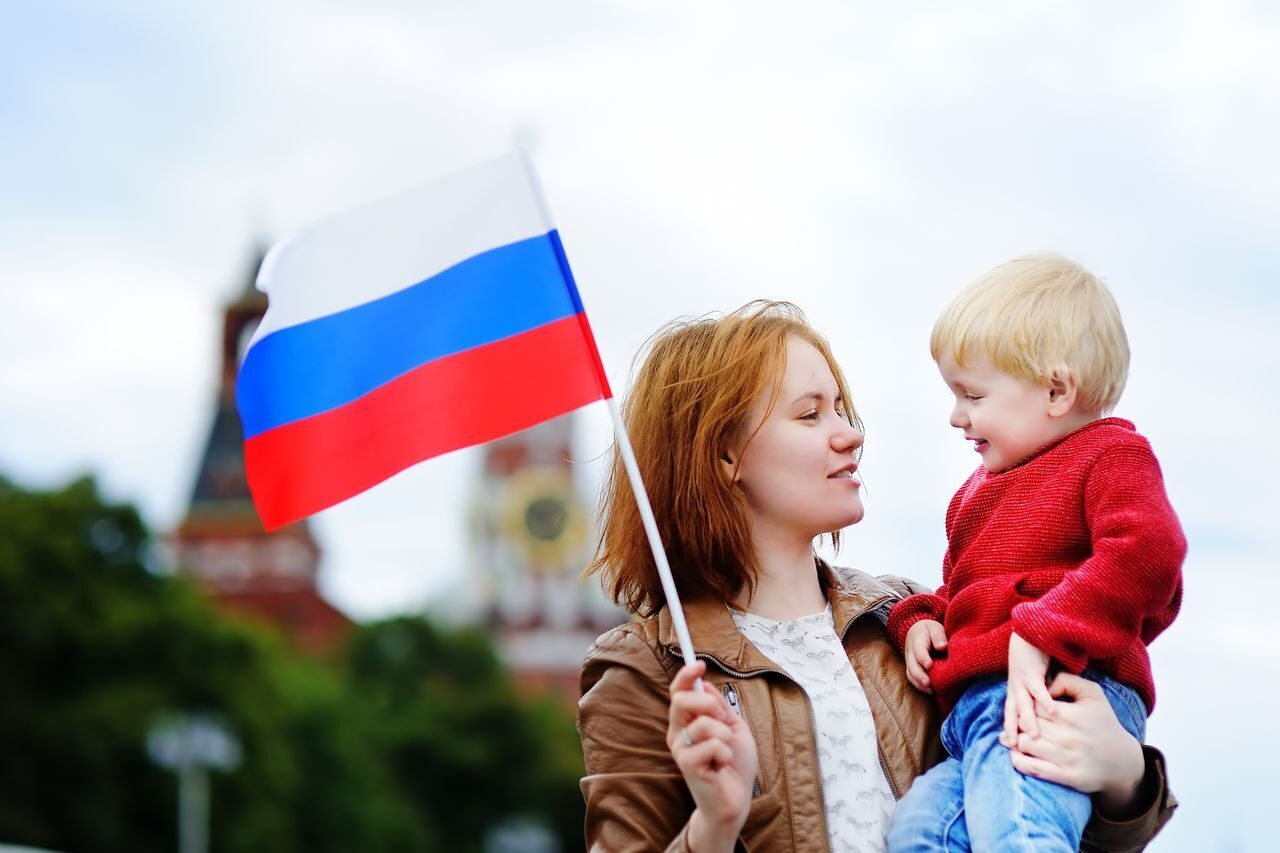 Young family with russian flag with Moscow Kremlin on background