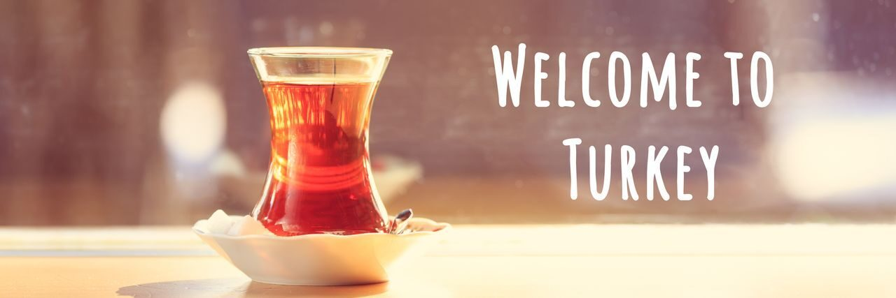 Hot turkish tea outdoors near glass wall. Turkish tea and traditional turkish culture concept. Welcome to Turkey text