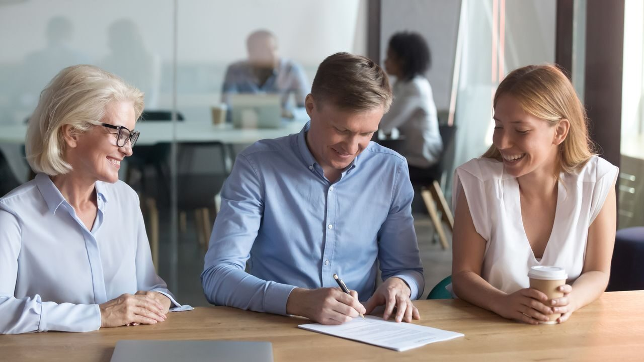 Excited young couple sign contract buying house together